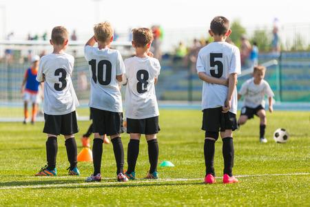 terrain foot: Match de football de football pour les enfants. Enfants en attente sur un banc.