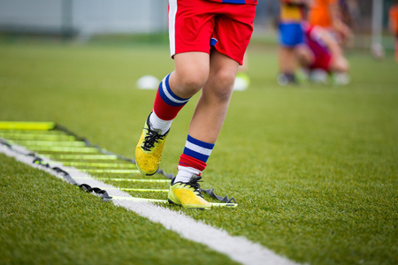 children sport: Ladder Drills Exercises for Football Soccer team. Young player exercises on ladder drills