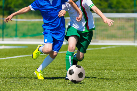 child feet: young boys playing football soccer game. Running players in blue and white uniforms