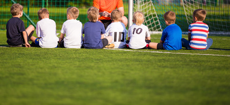 Football soccer match for children. Kids waiting on the game. breiefing with trainer