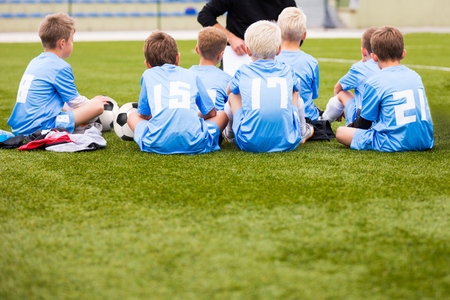 kids playing: soccer football coach tactic strategy speech. kids listening coach strategy speech. Stock Photo