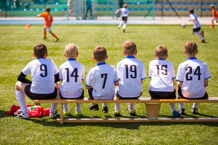 Football soccer match for children. Kids waiting on a bench. Archivio Fotografico