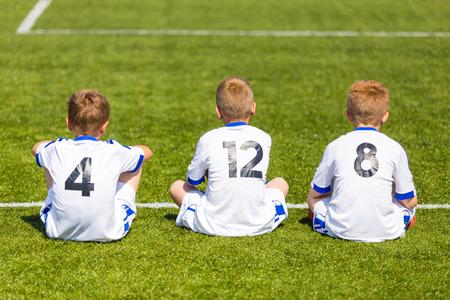 Voetbalwedstrijd voetbalwedstrijd voor kinderen. Kinderen wachten op een bankje.