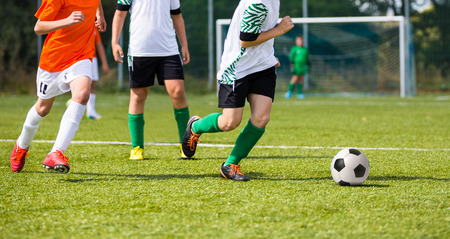 kids club: Football soccer game. Players footballers running and playing football match