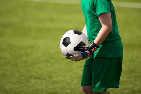 arquero de futbol: Portero infantil mantiene la pelota