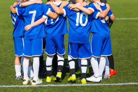 Coach geeft kinderen voetbalteam instructies. Jeugdvoetbal team voor finale