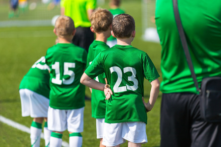 Young boys and soccer coach watching football match. Youth reserve players ready to play football tournament Stock Photo