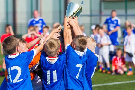 Jeunes footballeurs tenant le trophée. Garçons célébrant le championnat de football de football. Équipe gagnante du tournoi de sport pour enfants enfants. Banque d'images