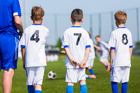 soccer coach: Young boys and soccer coach watching football match. Youth reserve players ready to play football tournament Stock Photo