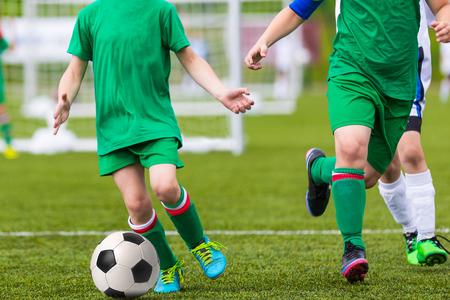 jugando futbol: Los muchachos que juegan al juego de fútbol soccer. Ejecución de los jugadores en uniforme azul y amarillo. juego final del torneo de fútbol para niños.
