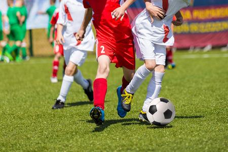 jugando futbol: Los muchachos j�venes que juegan al juego de f�tbol soccer. Ejecuci�n de los jugadores con uniformes rojos y blancos