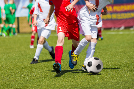 Young boys playing football soccer game. Running players in red and white uniforms Stock Photo
