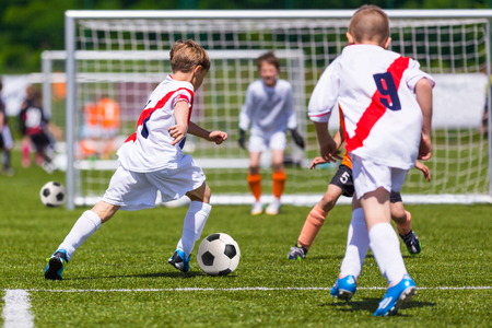 Training and football match between youth soccer teams. Young boys playing soccer game. Hard competition between players running and kicking soccer ball. Final game of football tournament for kids. Standard-Bild