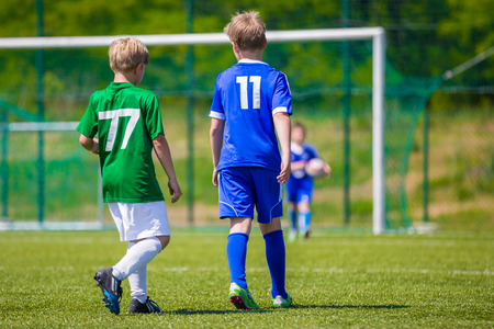 young boys: Training and football match between youth soccer teams. Young boys playing soccer game. Hard competition between players running and kicking soccer ball. Final game of football tournament for kids. Stock Photo