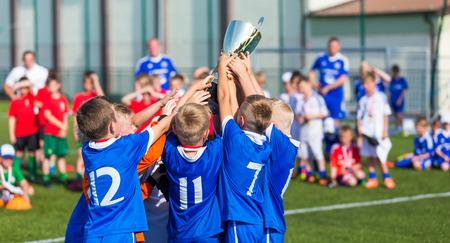 トロフィーを手にした若いサッカー選手。少年サッカー サッカー選手権を祝います。子供の子供のスポーツのトーナメントのチームを勝利します。