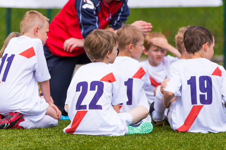 Coach giving children's soccer team instructions. Football; soccer; handball; volleyball; match for children. shout team, football soccer game. team work