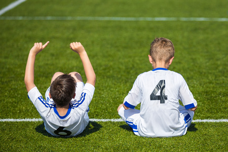 boy sitting: Childrens soccer match. Young boys reserve soccer players sitting on a sports field and watching football match ready to play. White uniforms of soccer players with numbers on the back. Stock Photo