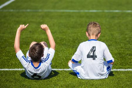 pies: partido de fútbol de los niños. Los muchachos se reservan jugadores de fútbol que se sienta en un campo de deportes y ver el partido de fútbol listo para jugar. uniformes blancos de jugadores de fútbol con números en la parte posterior.