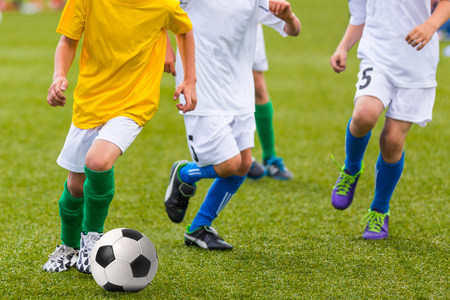 child feet: Training and football match between youth soccer teams. Young boys playing soccer game. Hard competition between players running and kicking soccer ball. Final game of football tournament for kids. Stock Photo