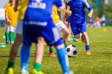 Adolescentes Niños que juegan a fútbol partido de fútbol. Los jugadores de fútbol jóvenes que se ejecutan y que golpea el balón de fútbol en un campo de fútbol.