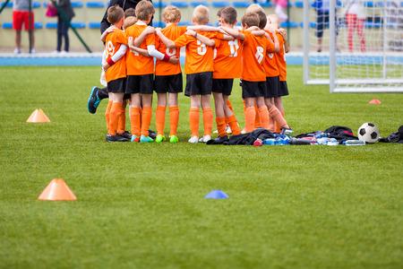 Jugend-Fußballfußballteam. Gruppenfoto. Fußball-Spieler, die zusammen stehen vereint. Fussball Team Huddle. Teamwork, Teamgeist und Teamkollegen Beispiel Lizenzfreie Bilder