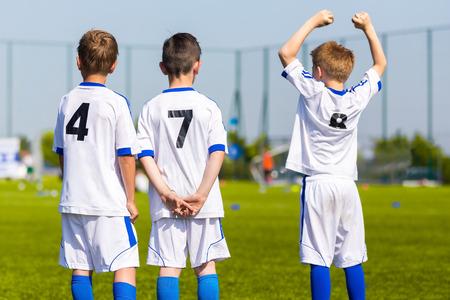 Jeugdsport team spelers ondersteunen teamgenoten op de sportwedstrijd