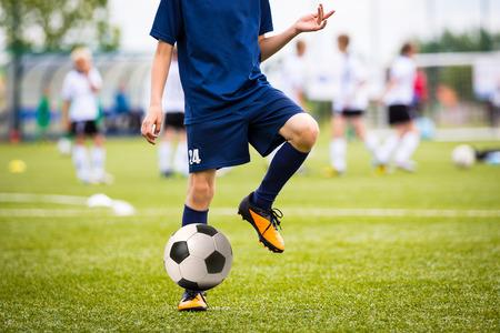 jugadores de futbol: Adolescentes Niños que juegan a fútbol partido de fútbol. Los jugadores de fútbol jóvenes que se ejecutan y que golpea el balón de fútbol en un campo de fútbol. Foto de archivo