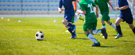 kids activities: Boys play soccer match. Blue and green team on a sports field
