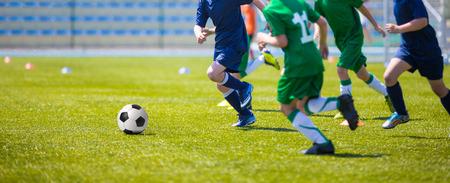 De jongens spelen voetbal wedstrijd. Blauwe en groene team op een sportveld