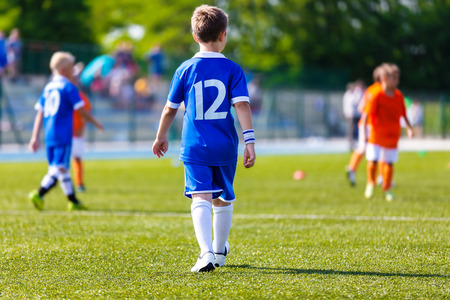 kids activities: Young boy as a soccer football player at a sports stadium. Youth soccer football match at school tournament.