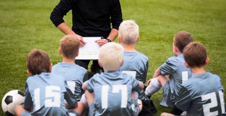 guidance: Coach Encouraging Boys Soccer Team. Soccer Football Team with Coach at the Stadium. Coach with Youth Soccer Team. Boys Listen to Coachs Instructions. Coach Giving Team Talk
