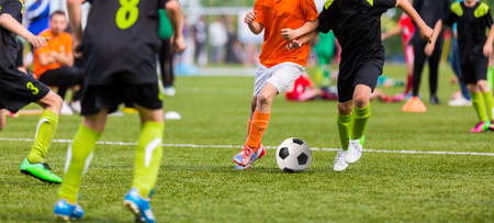 Young boys children in uniforms playing youth soccer football game tournament. Horizontal sport background.