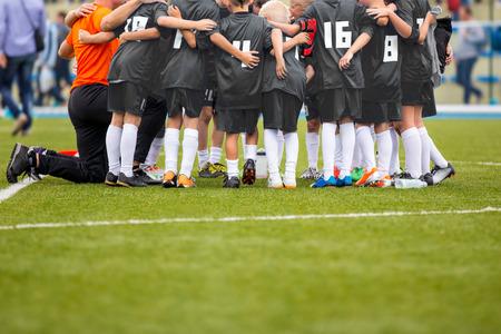 Young Boys w piłce nożnej w piłce nożnej z trenerem. Motywacja Dyskusja Przed Soccer Match. Chłopcy trochę League Soccer Team. Zdjęcie Seryjne