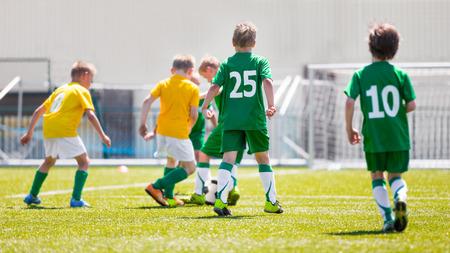 De jongens spelen voetbal wedstrijd. Gele en groene team op een sportveld