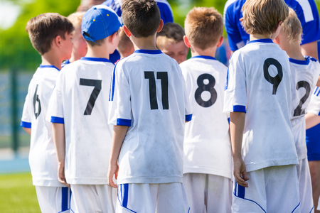 soccer team: Coach giving young soccer team instructions. Youth soccer team together before final game. Football match for children. Boys group shout team, gathering. Coach briefing. Soccer football background.
