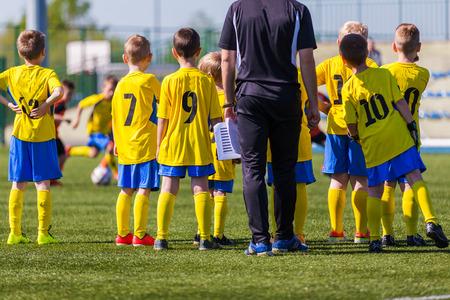 축구 경기를 관람하는 코치 및 청소년 축구 예비 선수. 코치 젊은 축구 팀 지침 제공합니다. 코치 브리핑 축구 축구 배경입니다. 스톡 콘텐츠