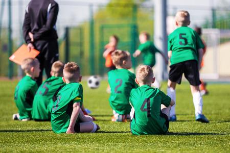 cerillos: equipo de fútbol juvenil juntos viendo el partido de fútbol. torneo de fútbol para los jugadores jóvenes. Niños sentados en un campo de deportes y el apoyo del equipo.