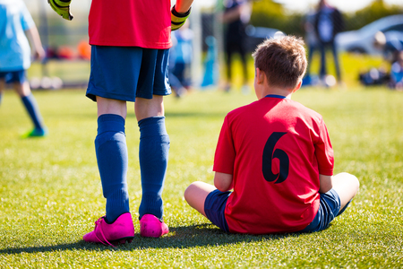 sports venue: Youth Soccer Player sitting on sports venue. Youth sports team supporting teammates at the game.