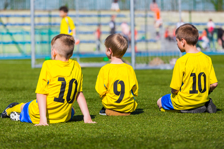sports venue: Group Of Young Boys Wearing Sport Outfit. Youth Soccer Players sitting on sports venue. Stock Photo