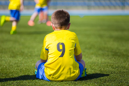 sports venue: Young Boy Wearing Sport Outfit. Youth Soccer Player sitting on sports venue and watching soccer game. Stock Photo