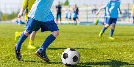 jugadores de futbol: chicos jóvenes que juegan al juego de fútbol soccer. jugadores corriendo en uniformes deportivos azules y amarillas
