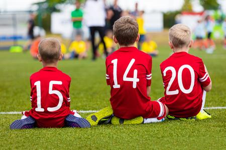 jugadores de futbol: Los muchachos en el equipo de fútbol sentados juntos en el campo de deportes. Los niños como Reserva de jugadores de fútbol de fútbol. torneo de fútbol partido de fútbol para los equipos de los niños. Foto de archivo
