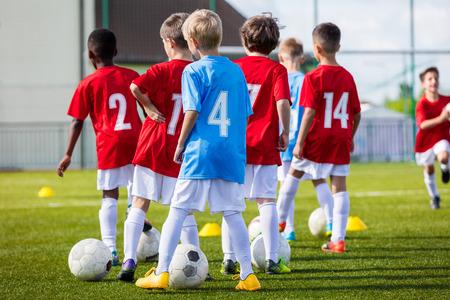 entrenamiento de fútbol de fútbol para el equipo de los chicos jóvenes antes del partido final del torneo de fútbol. Los muchachos que golpea el balón de fútbol en el campo de fútbol estadio