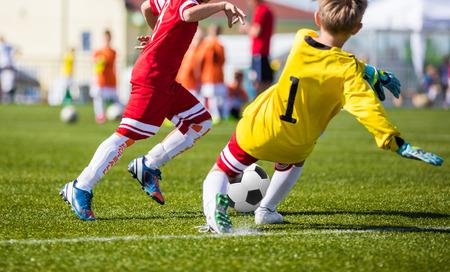 Voetbal voetbalwedstrijd. Spelers voetballers rennen en spelen voetbalwedstrijd. Forward jeugd voetballer tegen de keeper. Stockfoto