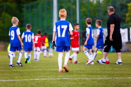 soccer coach: Football soccer match game for children. Youth sports team with soccer coach during football match at the stadium. Stock Photo