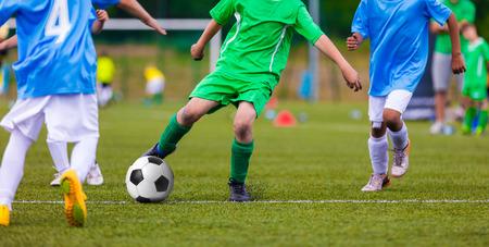 Jeugdvoetbal voetbalteams schoppen voetbal op een sportveld. Voetbaltoernooi voor jonge voetballers.