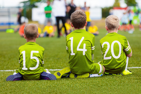 Young players of soccer team. Kids as reserve players on football bench watching soccer game and supporting green team. Soccer school tournament for youth soccer teams. Stock Photo