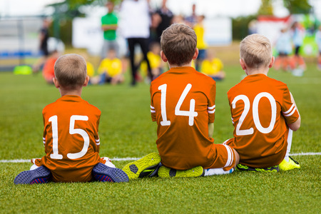 football play: Kids of young soccer football team. Boys in orange shirts as reserve players sitting on football pitch and watching soccer match.