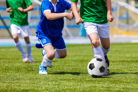 streichholz: Young boys kicking soccer football on the sports field. Youth blue and green teams tournament competition