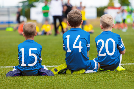 boyhood: Youth football soccer team sitting together on field and watching soccer match. Young boys as reserve players on bench supporting team